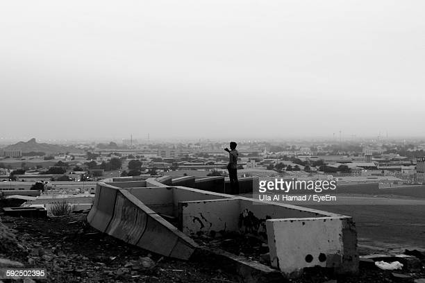 Man Standing At Abandoned Place In City Against Sky