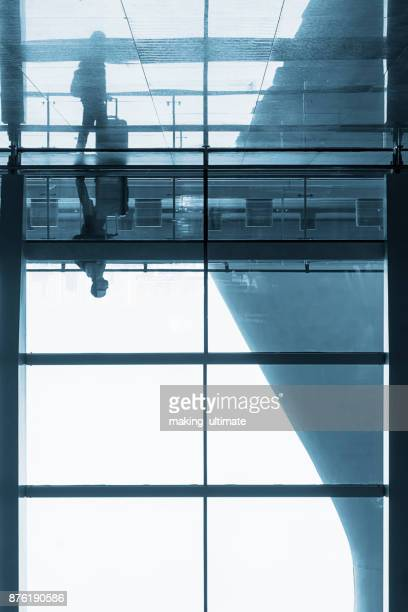man standing at airport window with lugagge
