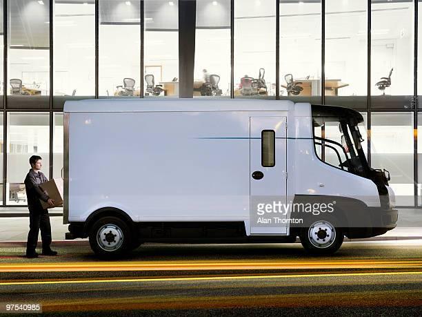 Man standing at back of electric van