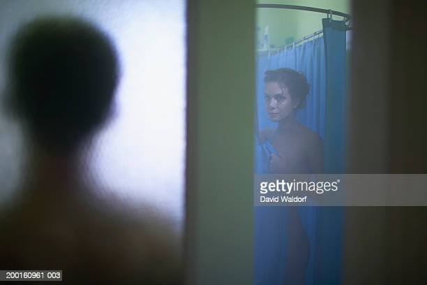 man standing at bathroom doorway while woman showers (focus on woman) - vouyer fotografías e imágenes de stock