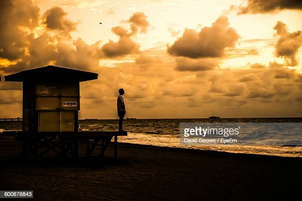 Man Standing At Beach Against Cloudy Sky During Sunset