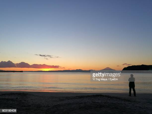 man standing at beach against sky during sunset - zushi kanagawa stock photos and pictures
