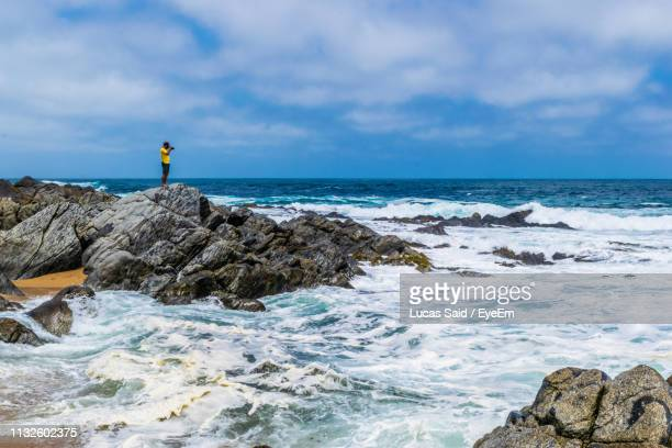 man standing at beach against sky - vina del mar stock pictures, royalty-free photos & images