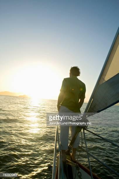 man standing at bow of sailboat looking at sunrise - mid adult men imagens e fotografias de stock