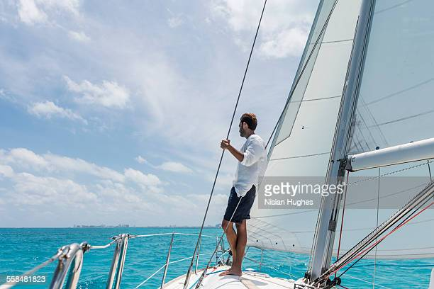 man standing at bow of sailboat looking out