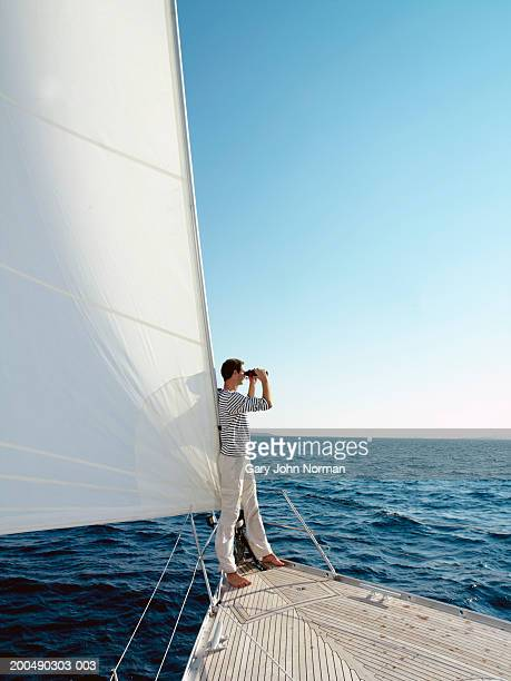 Man standing at bow of yacht, using binoculars