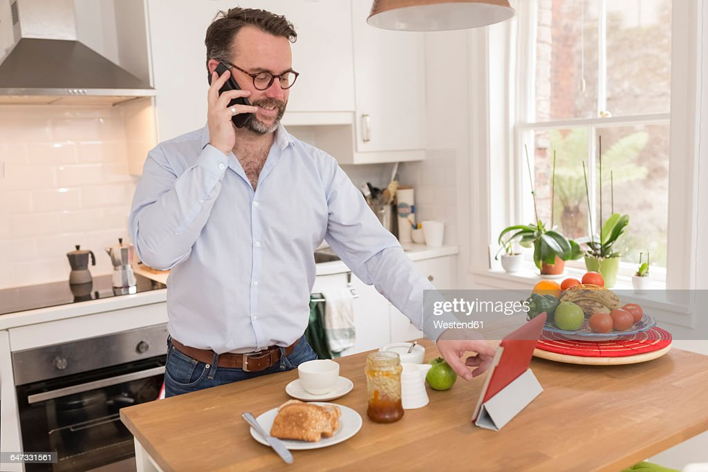 Man standing at breakfast table in the kitchen telephoning with smartphone while using digital tablet : Stock Photo