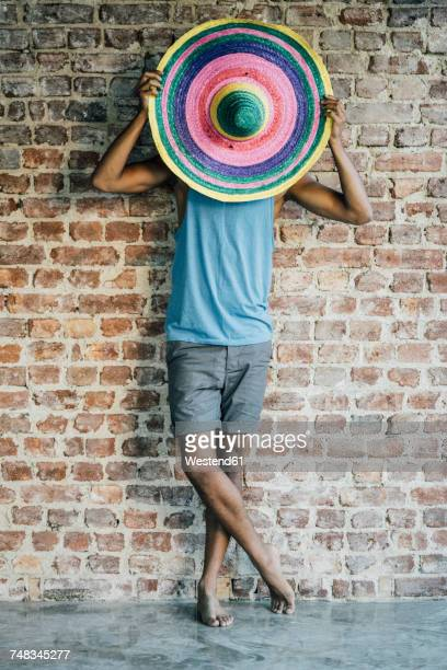 Man standing at brick wall covering his face with a sombrero