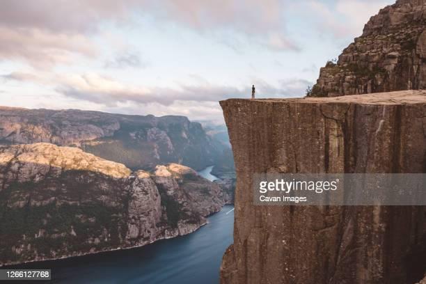man standing at edge of cliff at preikestolen, norway - スタバンゲル ストックフォトと画像