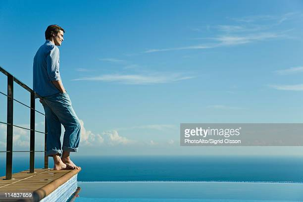Man standing at edge of infinity pool, looking at view