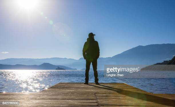 Man standing at edge of pier by lake
