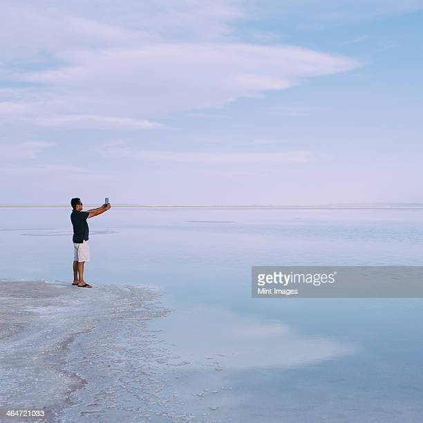 A man standing at edge of the flooded Bonneville Salt Flats at dusk, taking a photograph with a tablet device, near Wendover.