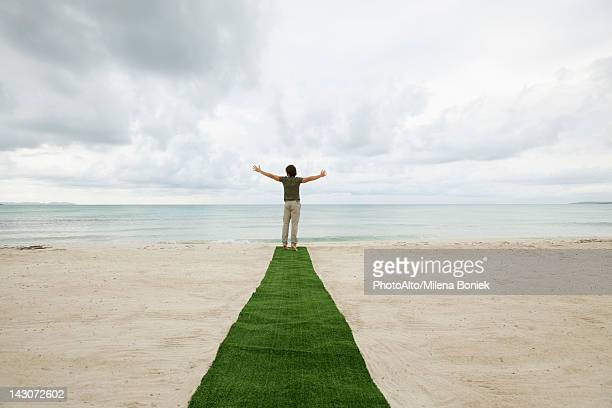 Man standing at end of carpet on beach with arms outstretched, rear view