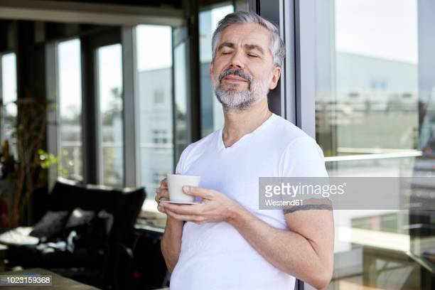 man standing at french enjoying cup of coffee - gelassene person stock-fotos und bilder