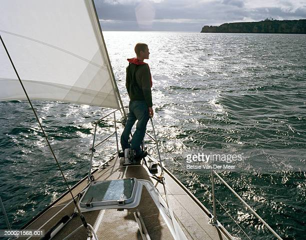 Man standing at front of sailing boat, rear view