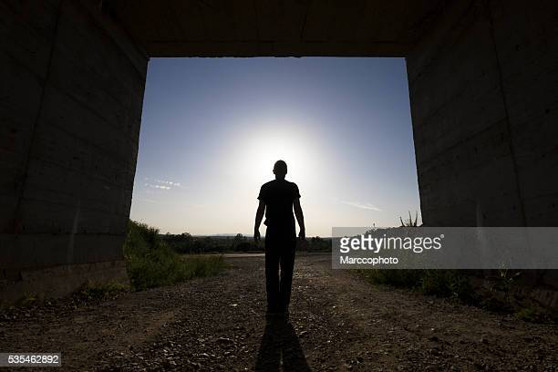 Man standing at large passage of concrete building, blocking sunlight