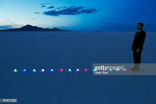 Man standing at line of glowing orbs in desert