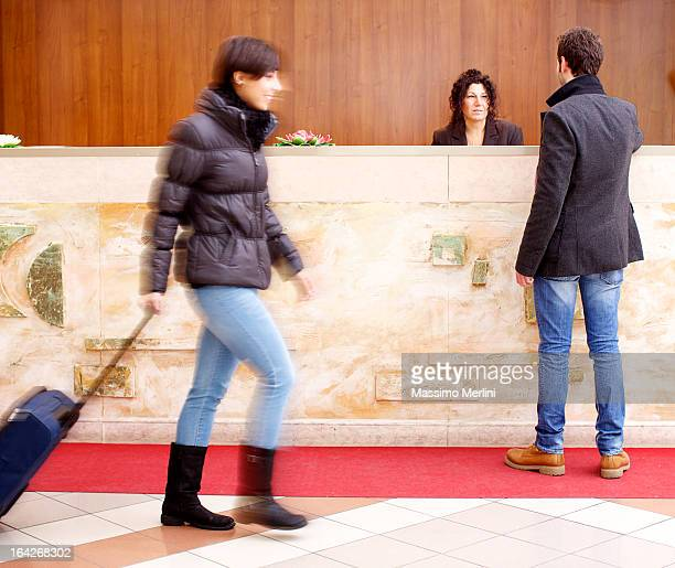 Man standing at reception desk in hotel lobby