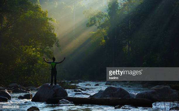A man standing at river rock under ray of light green forest shelter