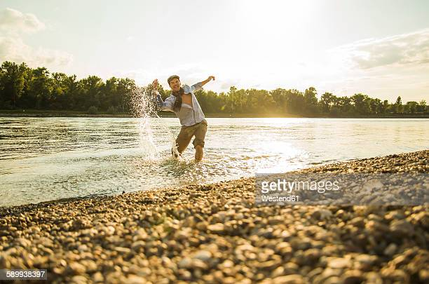 Man standing at riverside splashing with water