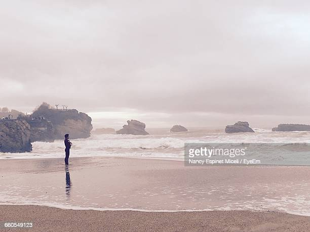 Man Standing At Sea Shore Against Cloudy Sky