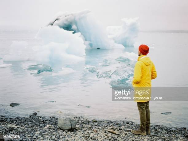 man standing at sea shore during winter - 防寒着 ストックフォトと画像