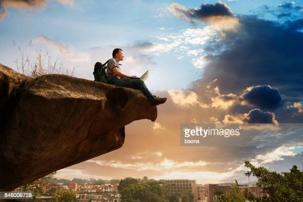 Man standing at the edge of a cliff using laptop