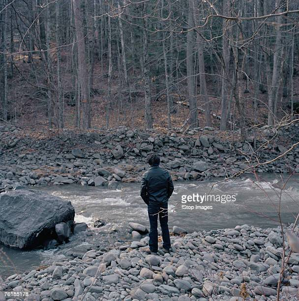 A man standing at the edge of a river