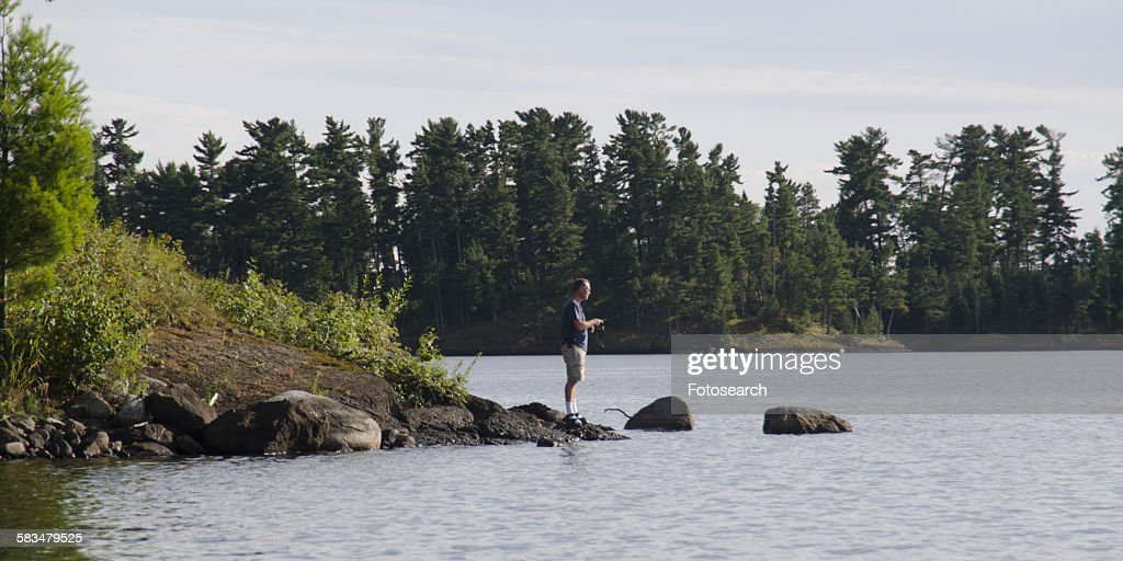 Man standing at the lakeside fishing : Stock Photo