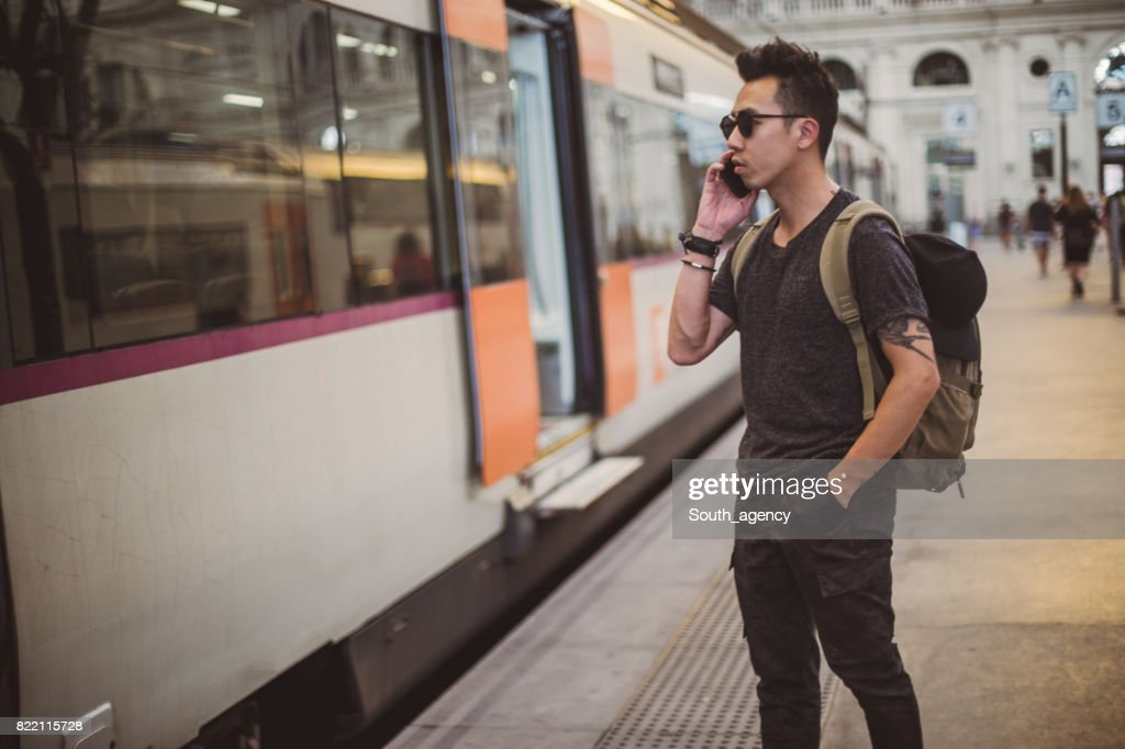 Man standing at train station and using phone : Stock Photo