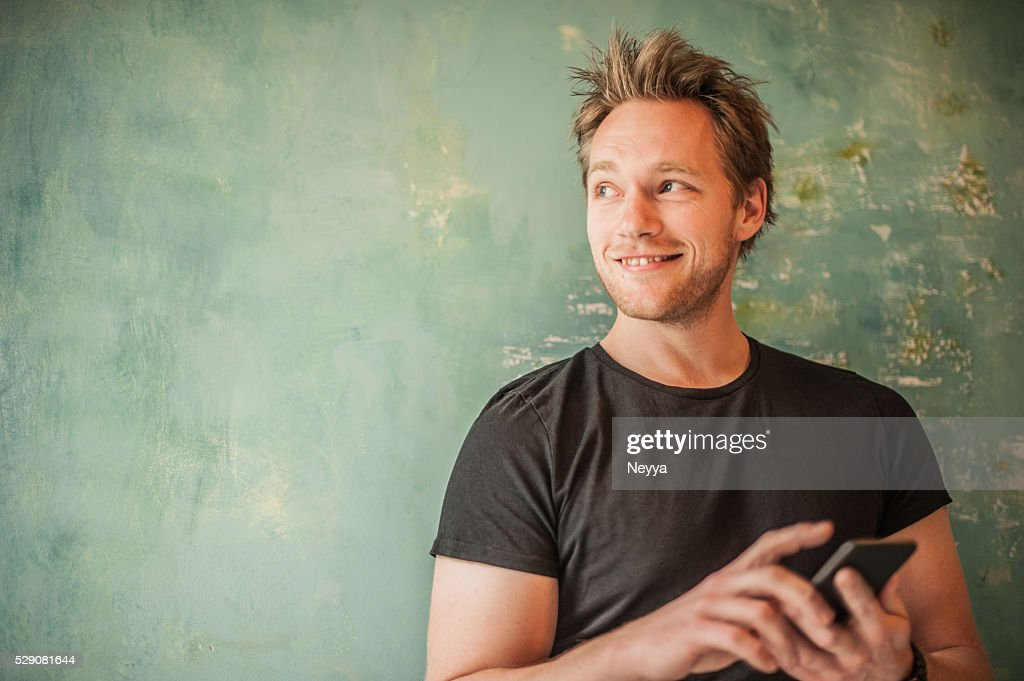 Man standing at wall, writting message and looking away : Stock Photo