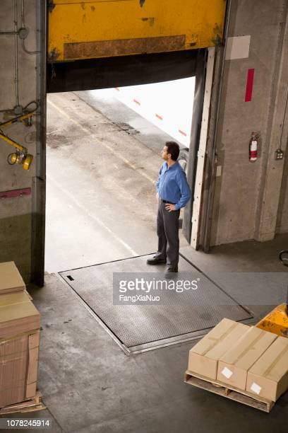 man standing at warehouse door to receive shipment - loading dock stock pictures, royalty-free photos & images