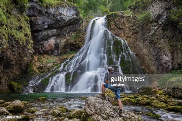 uomo in piedi alla cascata di golling - clima alpino foto e immagini stock
