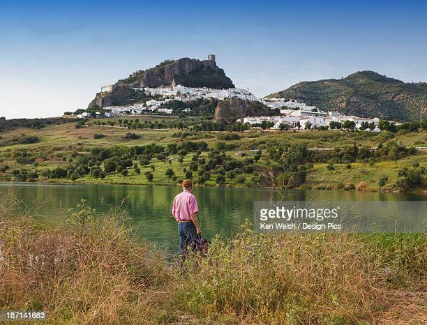 a man standing at water's edge looking at zahara de la sierra as seen over the zahara dam - cádiz fotografías e imágenes de stock