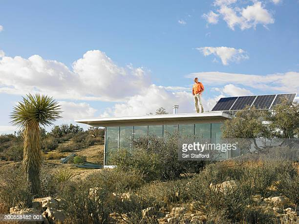 Man standing atop roof of prefabricated home with solar panels