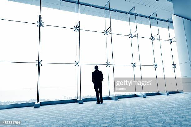 Man standing before large windows looking out