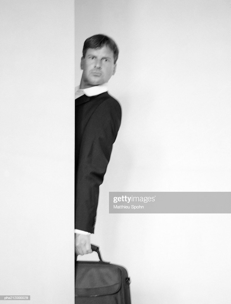 Man standing behind a wall, holding a bag, blurred b&w : Stockfoto