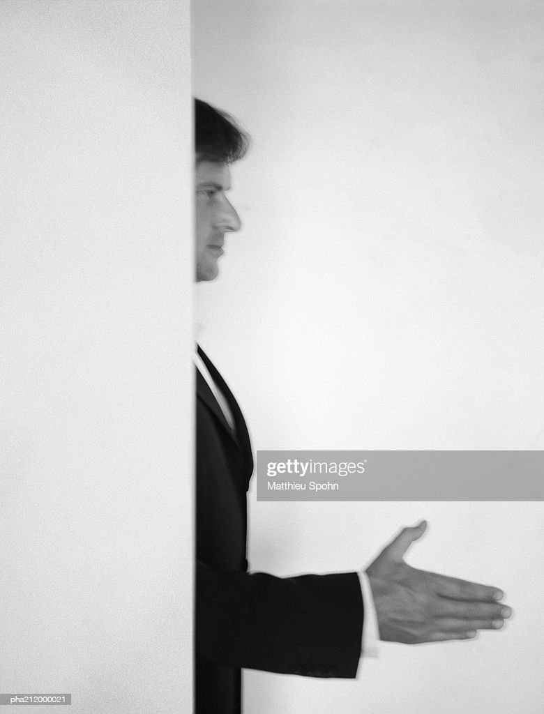 Man standing behind a wall, holding hand out, blurred, b&w. : Stockfoto