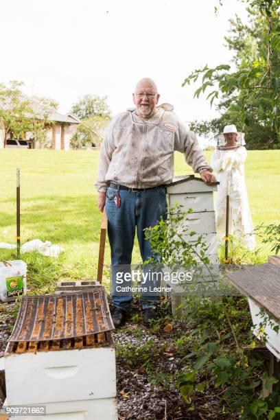 Man standing behind bee hives