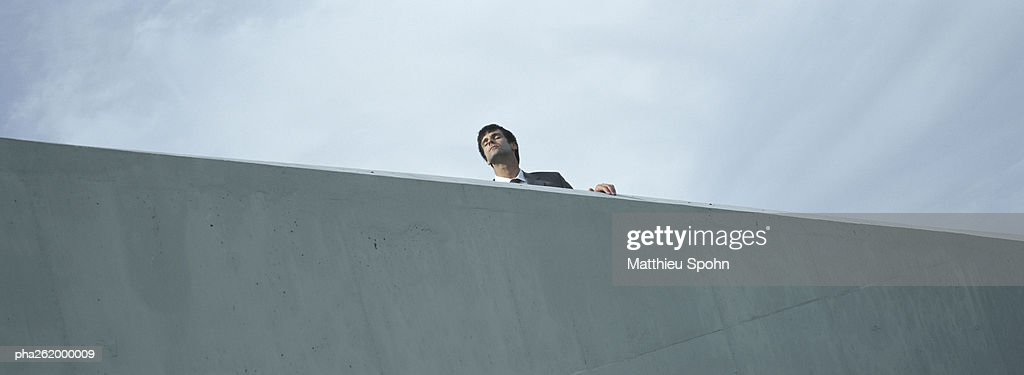 Man standing behind concrete wall, low angle view : Stockfoto