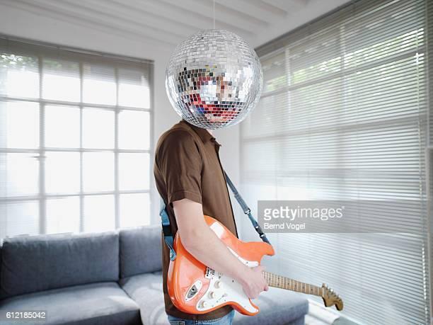 man standing behind disco ball - disco ball foto e immagini stock