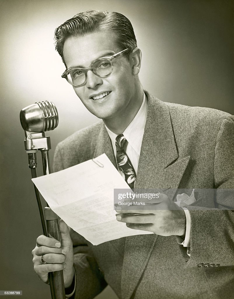 Man standing behind microphone : Photo