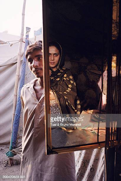 man standing behind mirror reflecting hijra - hijra pakistan stock pictures, royalty-free photos & images
