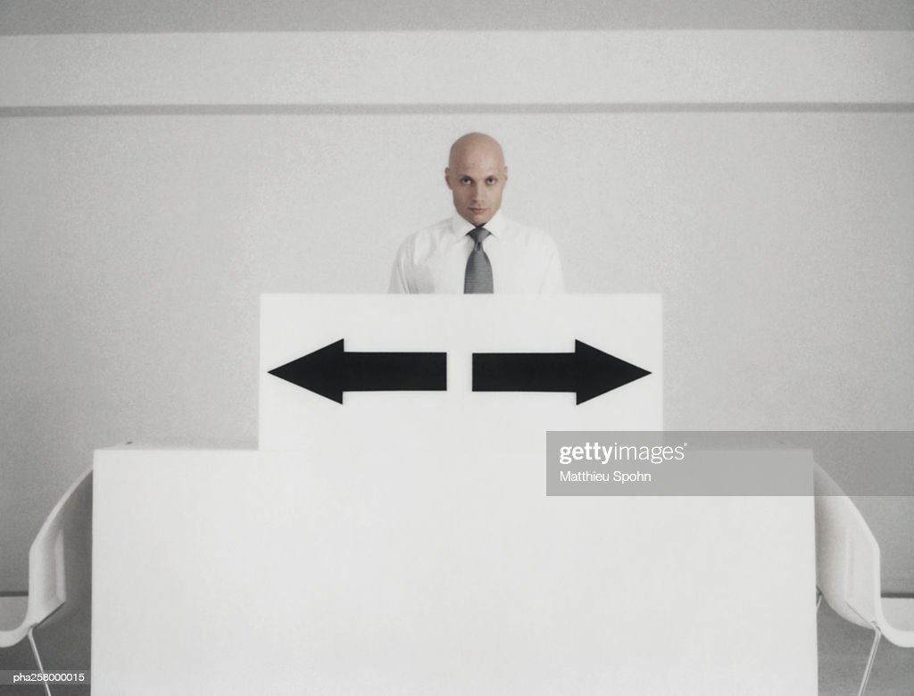 Man standing behind podium with two arrow signs pointing in opposite directions : Stockfoto