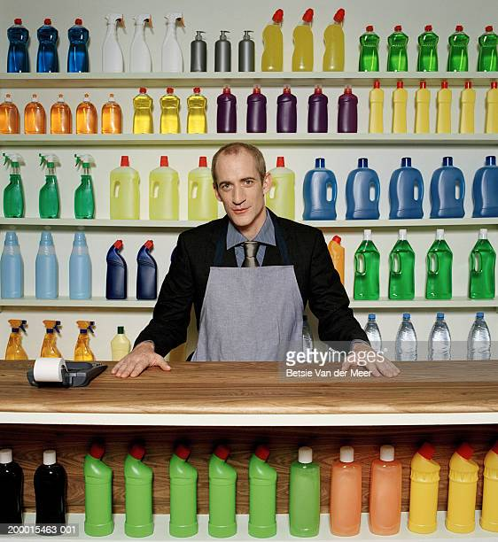 man standing behind shop counter, portrait - clorox bleach stock pictures, royalty-free photos & images