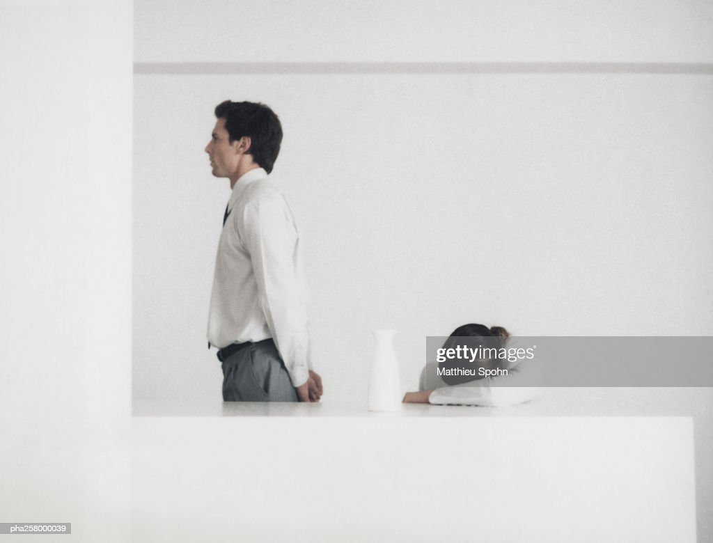 Man standing behind table, side view, woman with head down on arm : Stockfoto