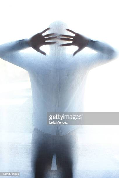 Man standing behind thin screen