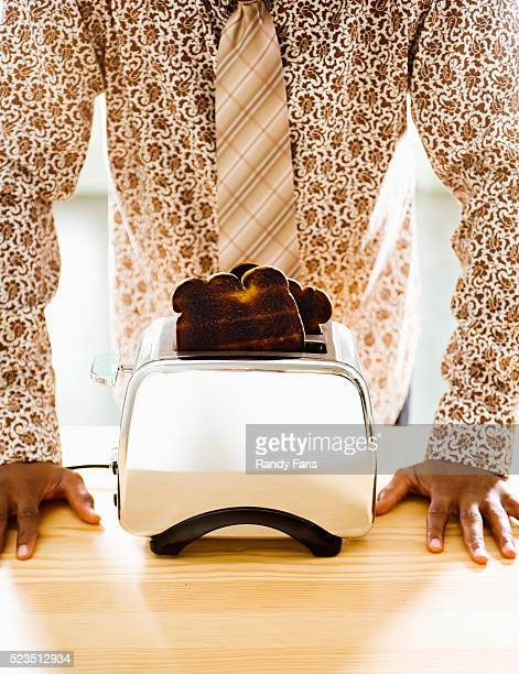 Man Standing Behind Toaster with Burnt Toast