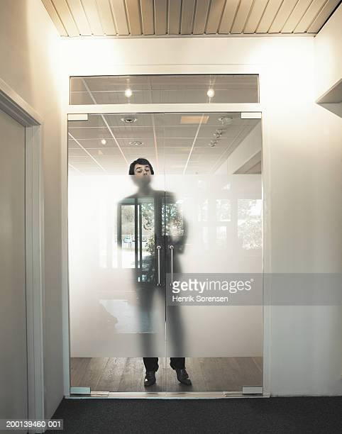man standing behind transparent reflecting doors, portrait - eyes wide shut foto e immagini stock