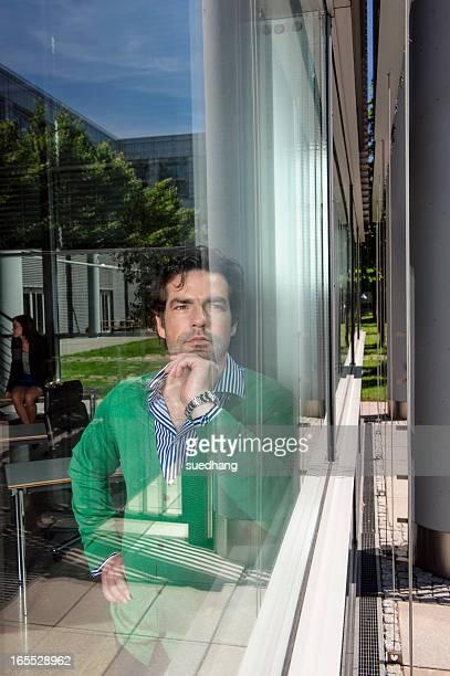 Man standing behind window